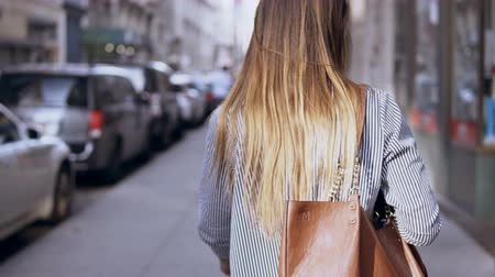 megalopolis : Back view of young beautiful woman with bag walking in the city centre of New York, America, exploring city.