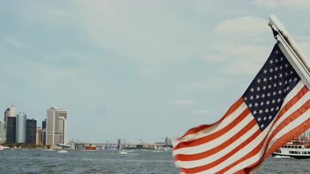 megalopolis : Beautiful view from the boar on Manhattan in New York, USA. American flag waving on the wind, East river. Stock Footage