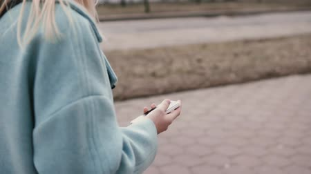 liga : Slow motion blonde woman in blue coat texting. Side view. Girl sending messages on the go. Lifestyle. High pace of life.