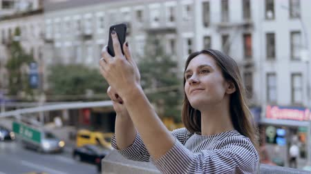 facetime : Young beautiful woman taking selfie photos on smartphone. Traffic road and busy cityscape on the background. Stock Footage
