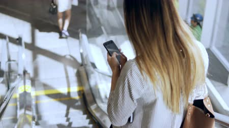 mozgólépcső : Young businesswoman working in modern office building. Busy female going down on escalator and using the smartphone.