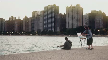 dusk : Young Beautiful couple on the shore of Michigan lake, Chicago, America. Woman draw, man play guitar. Stock Footage