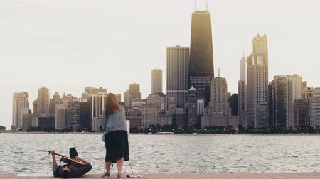 megalopolis : Young creative couple on the shore of Michigan lake, Chicago, America. Woman draw, ma play guitar lying on shore. Stock Footage