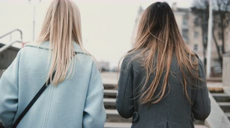 schody : Two ladies walk up from a pedestrian tunnel. Back view close up blonde and brunette females in stylish clothes chatting.