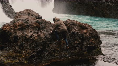 gullfoss : Young traveling man with camera exploring Iceland. Tourist climbs on the rock near the waterfalls and raises hands.