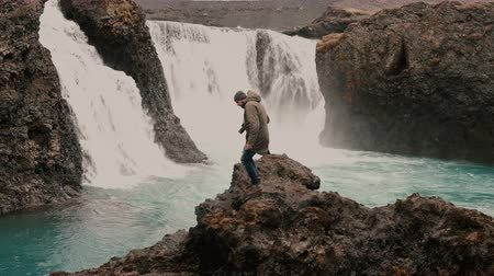 gullfoss : Young handsome man with camera walking alone in mountains valley near the powerful waterfall in Iceland.