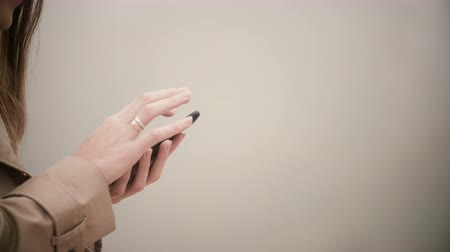 mãos : Close-up view of female hands typing on screen. Young woman using the smartphone with touchscreen in foggy day.