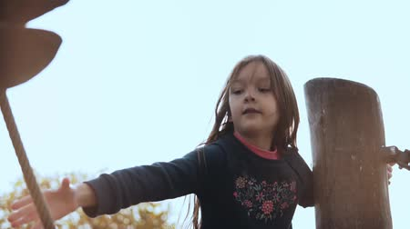 overcoming : Portrait of preschool girl in adventure park. Cute happy child with long hair goes through ropes course obstacles.