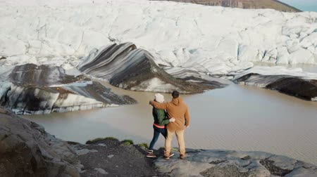 willpower : Young beautiful couple standing on the shore of the lake in Vatnajokull ice lagoon in Iceland and looking on glaciers.