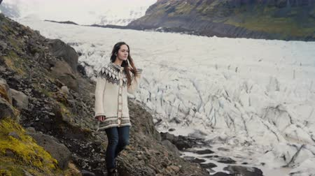 overcoming : Young traveling woman walking through the rocks in the mountains, exploring the Vatnajokull glaciers lagoon in Iceland. Stock Footage