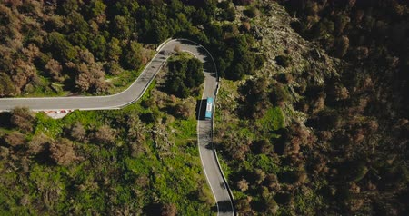 driveway : Blue bus turns left on a mountain road aerial view. Dangerous narrow forest driveway. Traffic road safety. Travel 4K.