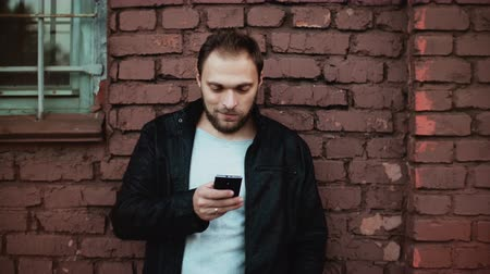 hírnök : Casual Caucasian man using smartphone outside. Handsome bearded young male businessman texting. Red brick wall 4K. Stock mozgókép