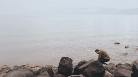 wandering : Caucasian man at the edge of Sea of Galilee. Big stones shore of Lake Tiberius, Kinneret. Israel. Religious pilgrim. 4K.