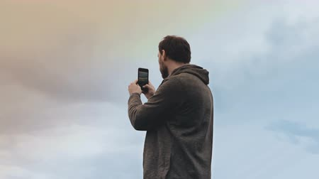 hacı : Bearded European man stands with smartphone. Low angle amazing sky view. Casual handsome male takes smartphone photo. 4K
