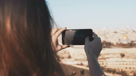 Иерусалим : Girl takes smartphone photos of Jerusalem, Israel. Female hands holding phone on a sunny day. Capturing moments. 4K. Стоковые видеозаписи