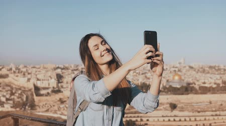 Иерусалим : Pretty girl takes selfie in Jerusalem old town. Cute local girl smiles happy, taking photos. Ancient Israel panorama 4K. Стоковые видеозаписи