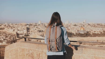 palestina : Happy European tourist female raises hands. Israel, Jerusalem. Girl with backpack walks to see old town panorama. 4K.