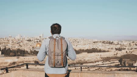Иерусалим : Excited European tourist male looks around. Israel, Jerusalem. Happy smiling man with backpack enjoys beautiful view 4K.