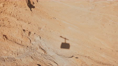 körképszerű : Shadow of a ropeway cabin rising in Masada desert. Aerial cable car going up on a sunny day. Sand and rocks. Israel 4K.