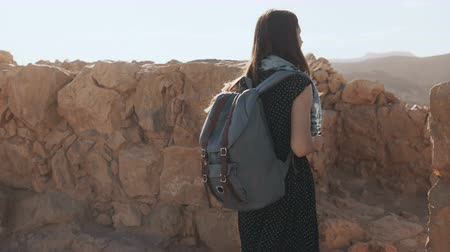 palestina : Woman with backpack walks among ancient walls. Attractive Caucasian female tourist enjoys mountain panorama. Masada. 4K.