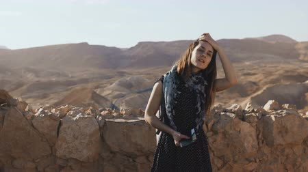 desert life : Girl with backpack looks at mountain panorama. Attractive European woman explores ancient ruins. Masada, Israel. 4K. Stock Footage