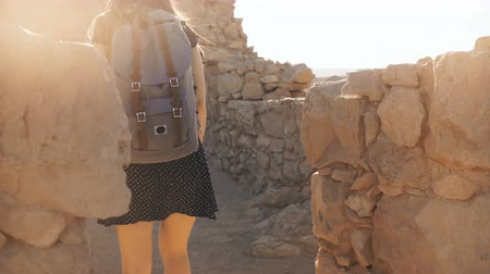 palestina : Girl with backpack explores ancient desert ruins. Pretty woman walks among mountain fortress walls in Masada, Israel. 4K