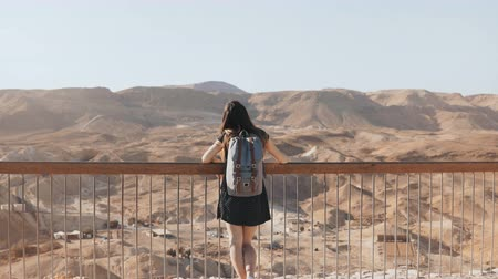 rock wall : Girl stands at huge mountain view, arms wide open. Pretty European woman happy and excited. Freedom. Masada, Israel. 4K Stock Footage
