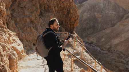 izrael : Male Caucasian tourist on ancient mountain road. Man with smartphone and camera enjoys historic desert Israel ruins. 4K