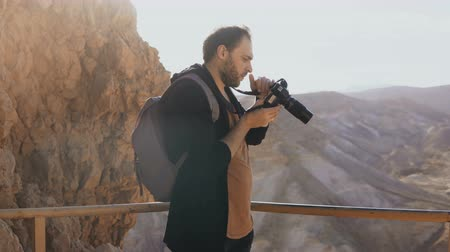 izrael : Man takes photos of massive mountain scenery. Caucasian male with camera photographs and looks at his camera. Israel 4K. Stock mozgókép