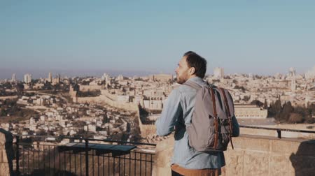 palestina : Happy Caucasian tourist male raises hands excited. Israel, Jerusalem. Man with arms wide open. Travel. Slow motion. Stock Footage