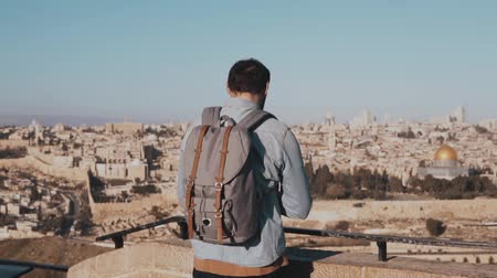 palestina : Man takes smartphone photos in Israel, Jerusalem. European tourist male enjoys ancient scenery. Travel. Slow motion. Stock Footage