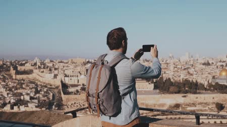 palestina : Male tourist takes smartphone photos of Jerusalem. European bearded man enjoys ancient town scenery. Israel. Slow motion Stock Footage