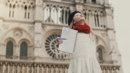 гордый : Little beautiful girl shows her picture at camera and smiling. Happy child near the Notre Dame in Paris, France.
