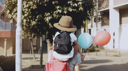 wanderlust : Mother carries son on shoulders among houses. Woman walking with a kid in hat and two air balloons. Lifestyle 4K.