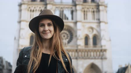 город : Portrait of young beautiful woman in hat standing near the Notre Dame cathedral in Paris, France and look at camera.