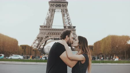 eiffel : Young happy couple walking, kissing near the Eiffel tower in Paris, France. Traveling man and woman on honeymoon. Stock Footage