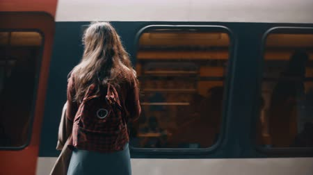 runaway : Back view of young student woman with backpack standing near in metro near the fast riding train, waiting for a trip. Stock Footage