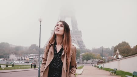 despreocupado : Young happy woman walking near the Eiffel tower in Paris, France. Tourist looking around and smiling. Slow motion. Stock Footage
