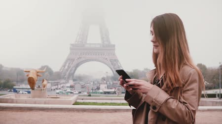 despreocupado : Portrait of young happy woman standing near the Eiffel tower in Paris, France and using the smartphone. Slow motion. Stock Footage