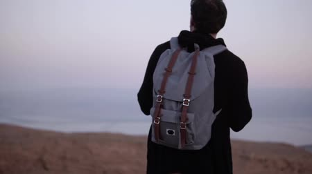 vándorlás : Man with backpack standing alone in dusk desert. Slow motion. Traveler looking at sunset sky. Searching for inspiration. Stock mozgókép