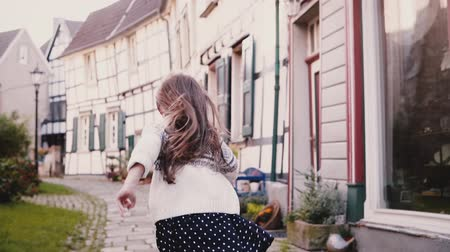 легкий : Little girl looks at camera, runs on paved road. Back view. Slow motion. Cute European child running in old street.