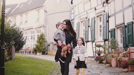 half timbered : European family walk together. Mother and two kids. Slow motion. Woman, boy and girl hold hands smiling. Love and care.