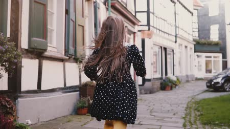 мощеный : Little girl in black dress running on old road. Back view slow motion. Half-timbered houses. Happy carefree childhood.