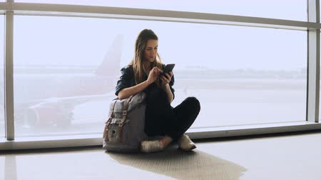 mensageiro : Pretty girl sits using phone by terminal window. European female passenger with backpack typing and smiling happy. 4K. Stock Footage
