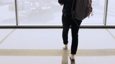 autêntico : Girl with backpack walks to airport lounge window. Female passenger with smartphone waits in terminal. Businesswoman. 4K Stock Footage