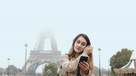 eiffel : Young beautiful woman standing near the Eiffel tower in Paris, France and using the smartphone in foggy morning. Stock Footage