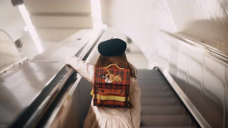 stair : Back view of little cute girl moving upstairs on the escalator. Child clothing the french style going to school.