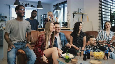 volný čas : Multi-ethnic students watch popular TV show. Medium shot 4K slow motion. Singing, laughing and smiling on couch. Emotion