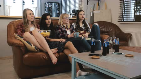 novela : Beautiful female friends discuss drama movie on TV. Young emotional girls watching sad romantic film 4K slow motion.