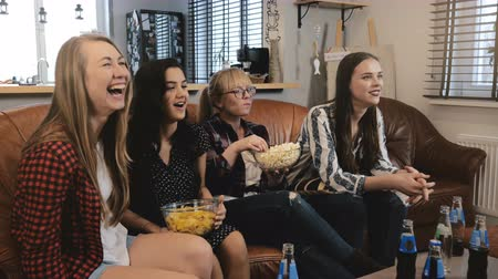 serial : Caucasian female friends watch popular TV show. Happy smiling girls watch funny action film at home 4K slow motion.